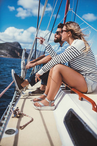 Young couple sitting together on a yacht