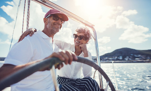 Senior couple having fun sailing at the wheel of a yacht
