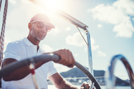 Retired active senior confidently steering his boat