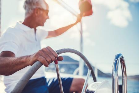 Senior man at the wheel of a yacht