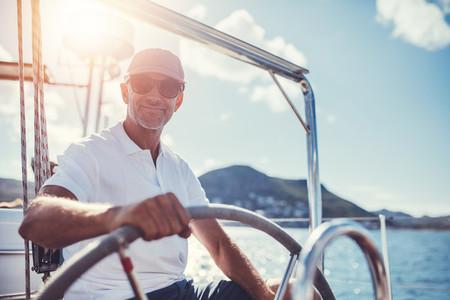 Confident senior man steering his boat