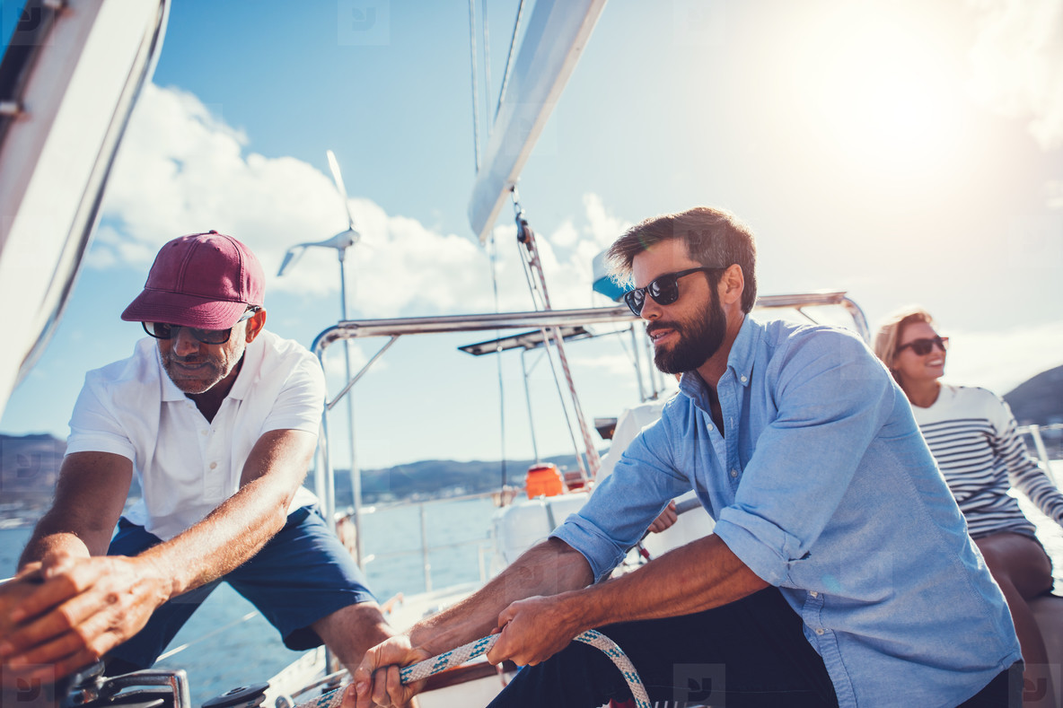 Father and son pulling rope to adjust sail on boat