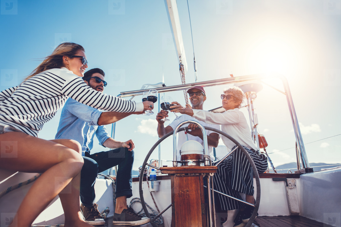 Happy family toasting wine glasses on a luxury yacht