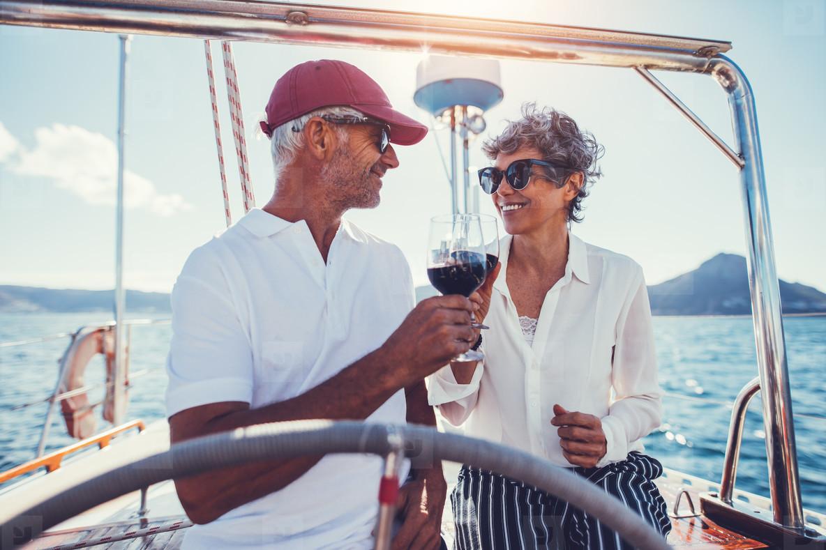 Romantic senior couple having wine on a yacht