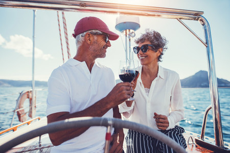 Romantic senior couple having wine on a yacht