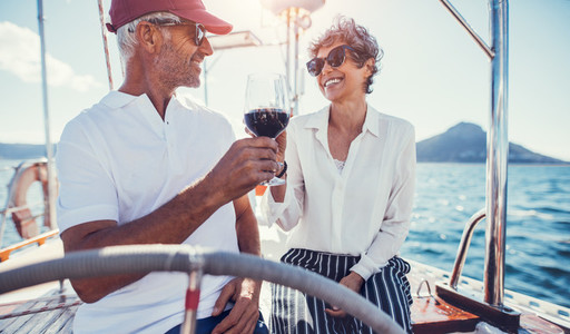 Happy senior couple enjoying wine on yacht