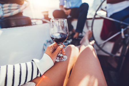 Red wine glass in hand of a woman on boat