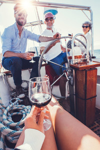 Woman having red wine on the boat with friends in background