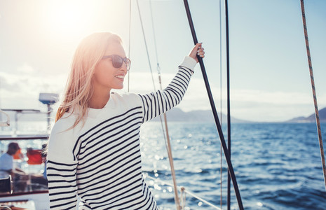 Woman on sailboat enjoying a beautiful day on vacation