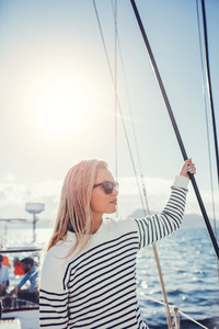 Attractive young woman standing on a yacht
