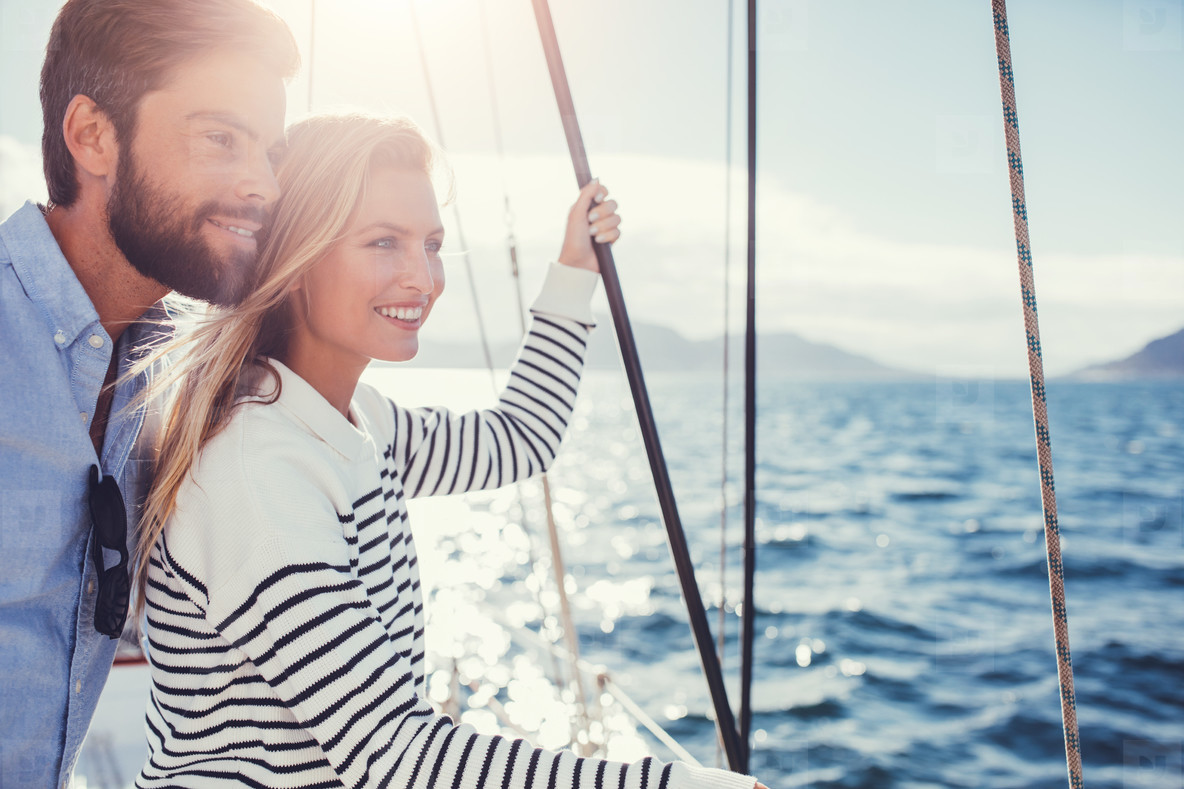 Happy young couple on sail boat looking at a view
