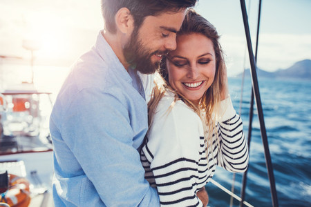 Romantic young couple standing on sailboat