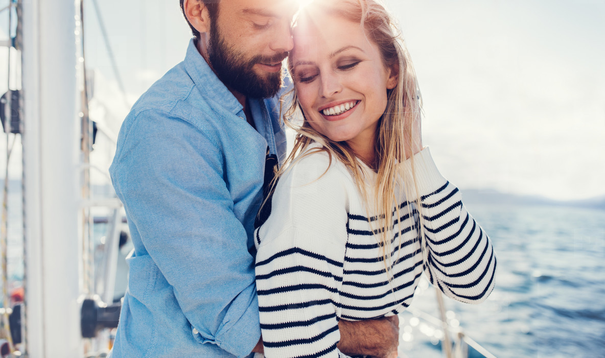 Affectionate young couple standing on boat