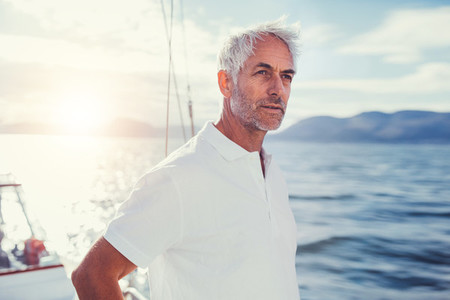 Handsome senior man standing on a boat