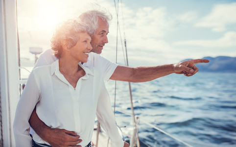 Smiling senior couple on yacht looking away