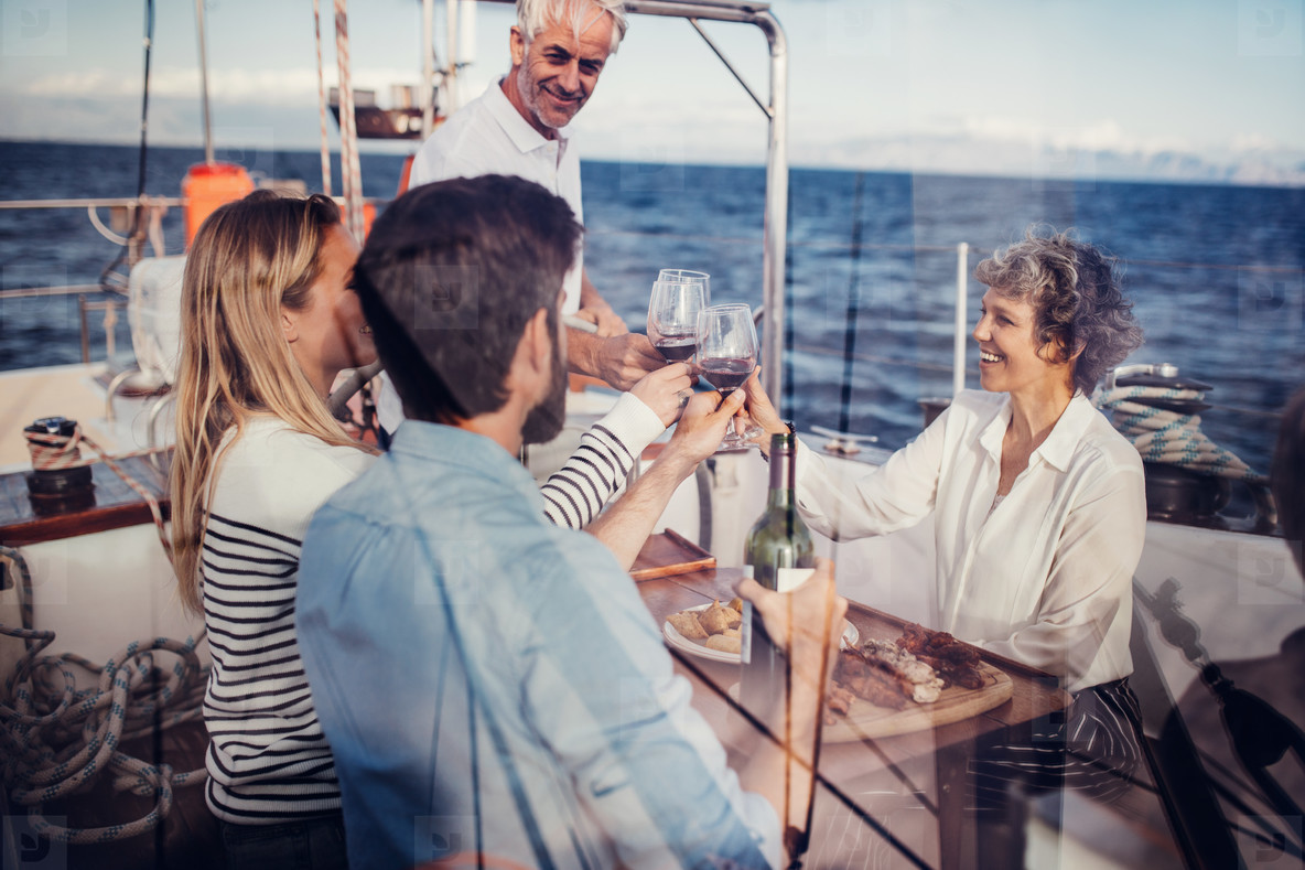 Senior and young couple on a yacht toasting wine