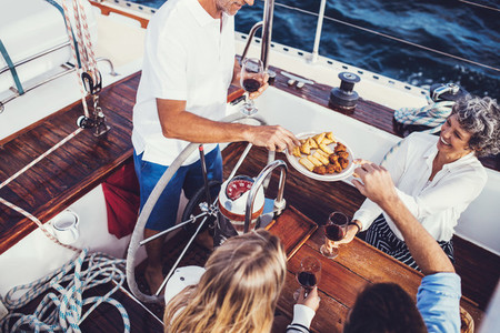 Mixed aged people on the yacht having food and drinks