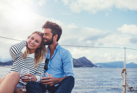 Affectionate couple on the deck of a yacht and having wine