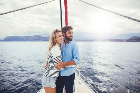 Romantic young couple standing together on a yacht