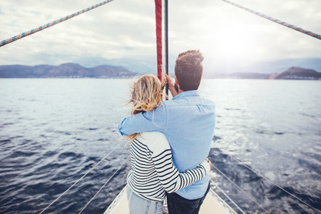 Loving young couple standing in the front of a yacht