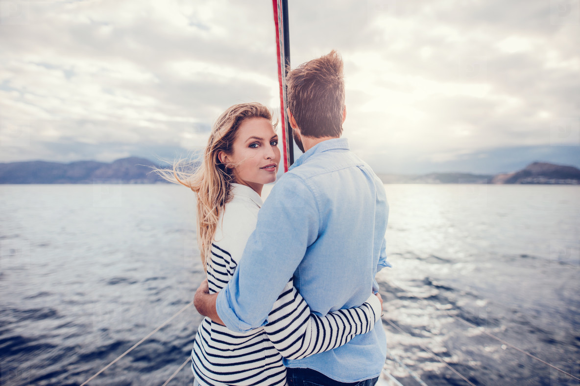 Young couple on vacation standing on a boat