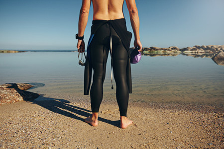 Young man standing on lake wearing wetsuit