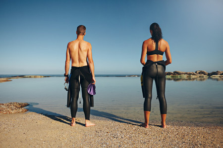 Young athletes standing on beach preparing for triathlon