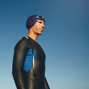Determined male triathlete in wetsuit