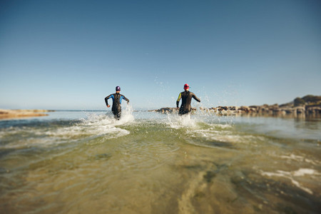 Two triathletes rushing into water for swim portion of race