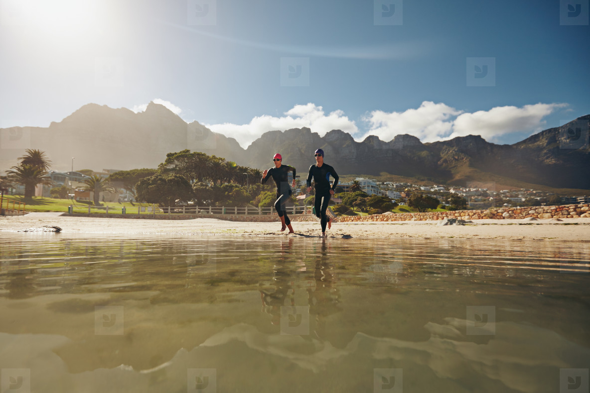 Two triathletes running into the water
