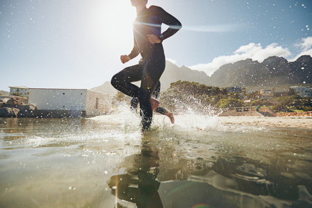 Young athlete running into water
