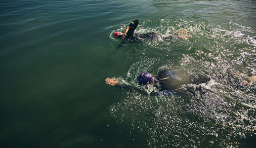 Athletes practicing swimming for triathlon race