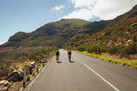 Triathletes practicing cycling on open country road