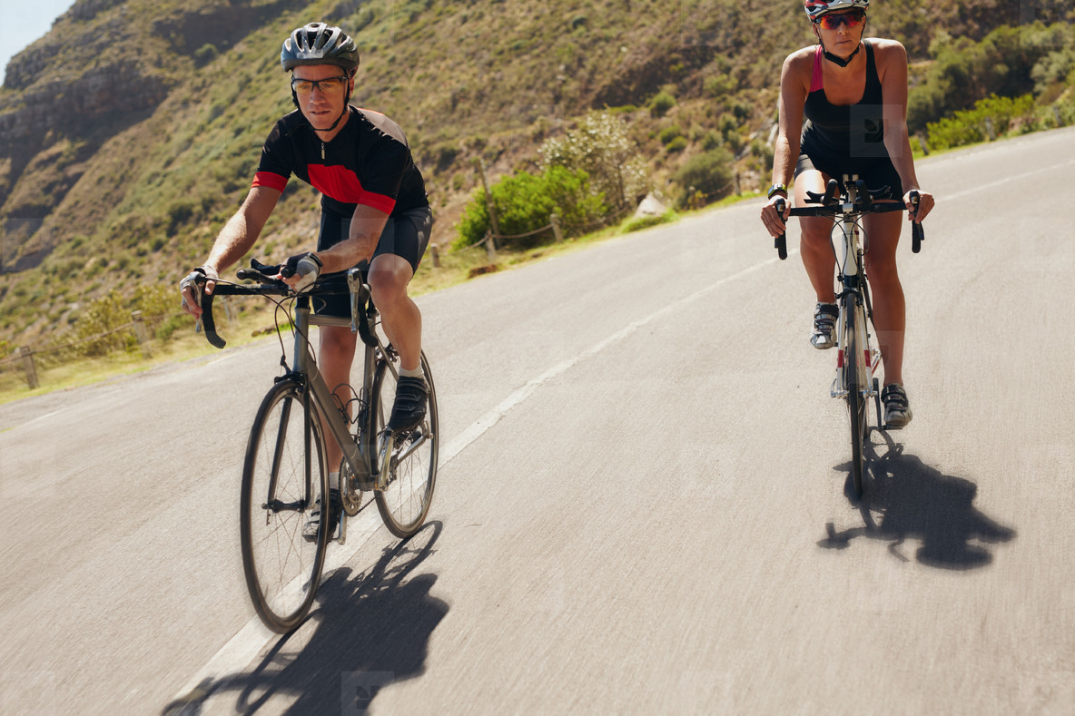 Man and woman cyclist riding down the country road