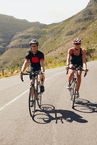 Couple of cyclists riding bicycles on a country road