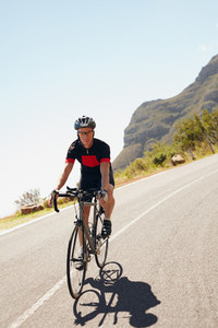 Male cyclist riding down a country road