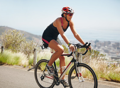 Female athlete riding cycle on country road