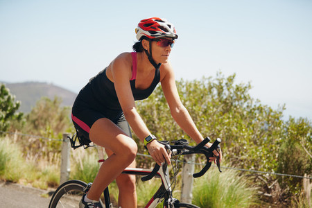 Young woman triathlon athlete cycling on country road