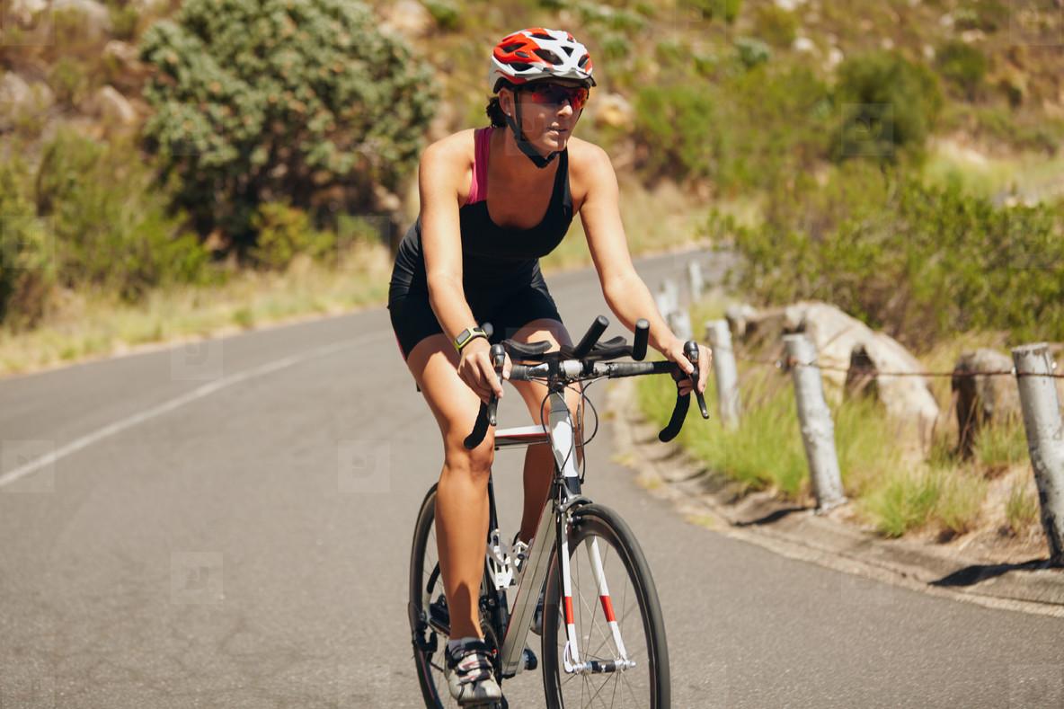 Young woman triathlon athlete cycling