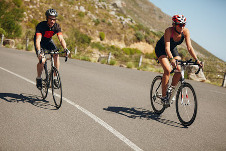 Triathletes riding bicycle on open road