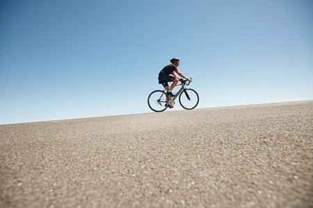 Male cyclist riding on a flat road against blue sky