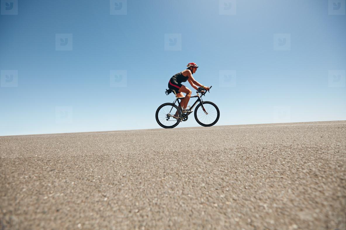 Female cyclist on a country road training for triathlon
