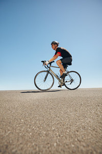 Male cyclist riding bicycle on flat road