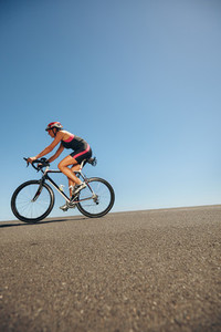 Female athlete training for cycling event of a triathlon