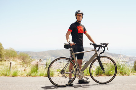 Young athletic man taking break after good cycling workout
