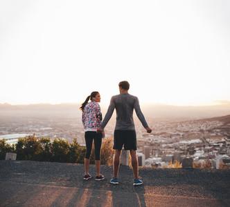 Joggers standing on hillside in morning