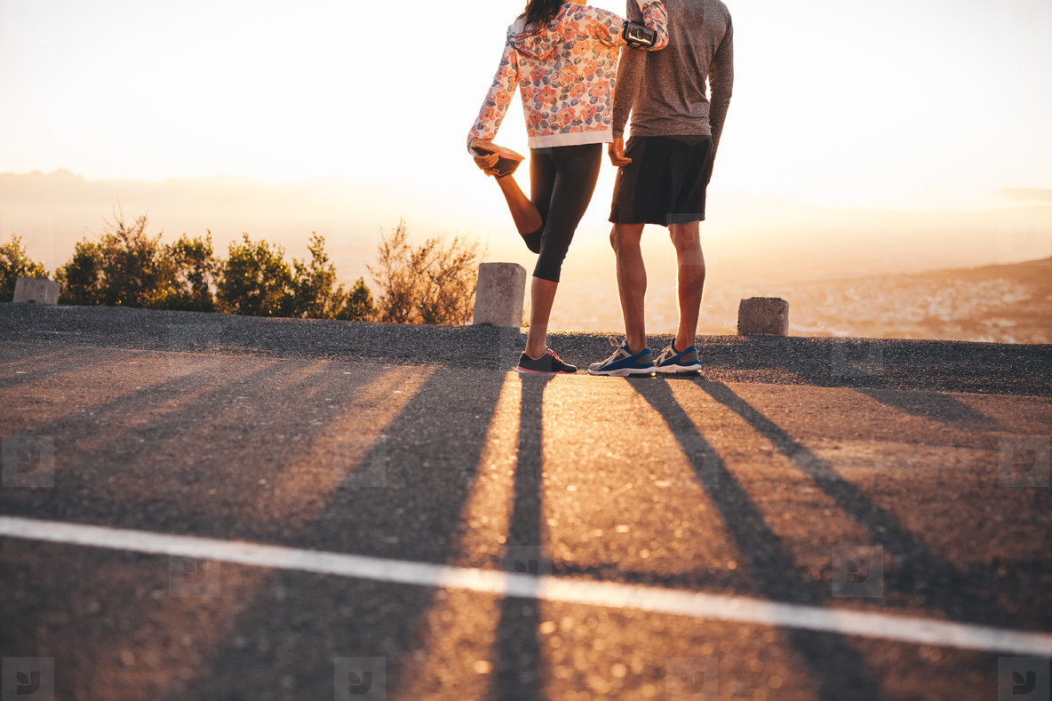 Couple of joggers looking at sunrise