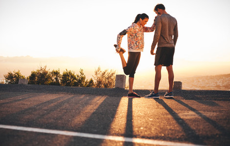 Fit young couple warming up before a run together