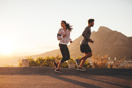 Young couple jogging on country road