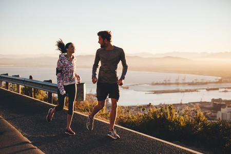 Two people running on a country road in morning